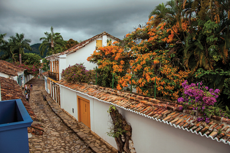 street lamp: Paraty, Brazil - January 23, 2015. View of people in alley with stone sidewalk and old houses on cloudy day in Paraty, an amazing and historic town totally preserved in Rio de Janeiro State coast