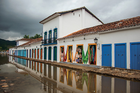 Paraty, Brazil - January 23, 2015. View of shops in old houses at alley with flooded stone walkway in Paraty, the historic town totally preserved in Rio de Janeiro State coast, southwestern Brazil