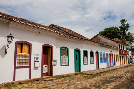 street lamp: Paraty, Brazil - January 26, 2015. Overview of cobblestone street with old houses under blue cloudy sky in Paraty, an amazing and historic town in Rio de Janeiro State coast, southwestern Brazil