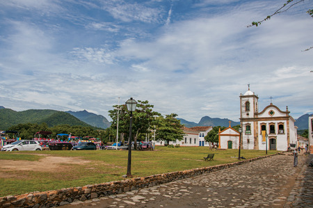 street lamp: Paraty, Brazil - January 26, 2015. Cobblestone street with old church under restoration and cars in Paraty, an amazing and historic town totally preserved in the coast of Rio de Janeiro State