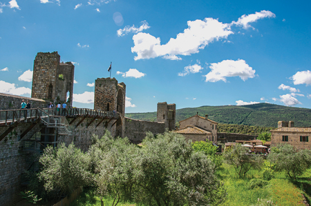 View of buildings and trees from above the walls of the Monteriggioni hamlet. A medieval fortress, surrounded by stone walls, at the top of a hill, near Siena. Located in the Tuscany region Stock Photo
