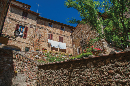 View of stone wall, old buildings with flowering plants and blue sky at Colle di Val dElsa. The village with its historic center preserved and known by its crystal production. In the Tuscany region Stock Photo