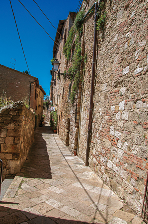 View of narrow alley with old buildings and lamps in Colle di Val dElsa. The graceful village with its historic center preserved and known by its crystal production. Located in the Tuscany region