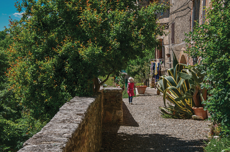 Street view with pebble walkway, flowering plants and little girl in the background in the town of Colle di Val dElsa. A graceful village with its historic center preserved. In the Tuscany region