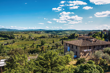 Overview of house with green Tuscan hills in the background and blue sky at San Gimignano. An amazing medieval town famous for having several towers in its historical center. Tuscany region