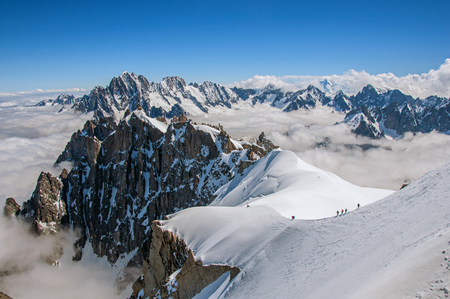 Snowy peaks and mountaineers in a sunny day, viewed from the Aiguille du Midi, near Chamonix. A famous ski resort located in Haute-Savoie Province, at the foot of Mont Blanc in the French Alps.