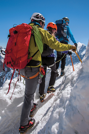 Close-up of climbers walking on snowy path in the sunny day at the Aiguille du Midi, near Chamonix. A famous ski resort located in Haute-Savoie Province, at the foot of Mont Blanc in the French Alps.