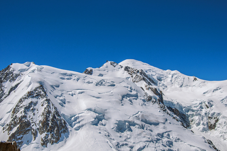 Snowy Mont Blanc in a sunny day, viewed from the Aiguille du Midi, near Chamonix. A famous ski resort located in Haute-Savoie Province, at the foot of Mont Blanc in the French Alps.