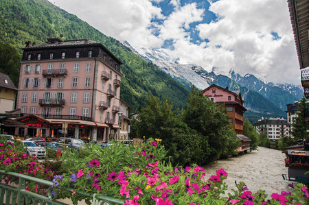 Chamonix, France - June 26, 2016. View of building, creek, flowers and the Mont Blanc in Chamonix, the famous ski resort located in Haute-Savoie Province, at the foot of Mont Blanc in the French Alps