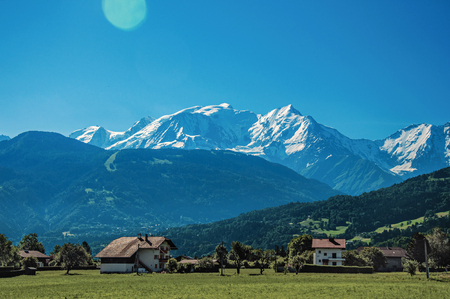 Fields, cottages and alpine landscape in a sunny day, near Saint-Gervais-Les-Bains. A famous ski resort located in Haute-Savoie Province, near the Mont Blanc in the French Alps.