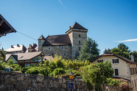Partial view of Annecy castle and houses with a wall in foreground and blue sky, city center of Annecy. Located in the department of Haute-Savoie, Auvergne-Rhone-Alpes region, south-eastern France.