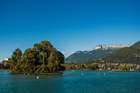 View of Annecy lake, with island, vegetation, mountains and blue sky in background. Located in the department of Haute-Savoie, Auvergne-Rhone-Alpes region, south-eastern France. Stock Photo
