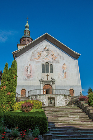 Church facade with steeple and paintings. At the historical hamlet of Conflans, near Albertville. Located in the department of Haute-Savoie, south-eastern France.