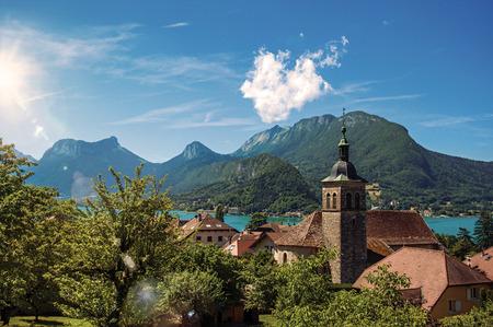Widok na domy i dzwonnicę z krajobrazem gór błękitnego nieba, w miejscowości Talloires. Urocza wioska nad jeziorem Annecy. Departament Górnej Sabaudii, południowo-wschodnia Francja. Wyretuszowane zdjęcie Zdjęcie Seryjne