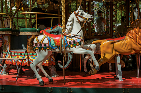Colorful carousel with white horse in a park of Annecy. An historical and lovely lakeside town located in the department of Haute-Savoie, south-eastern France.