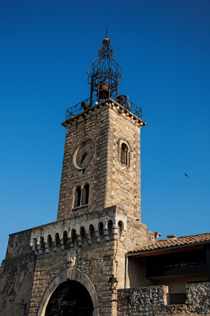 Close-up of old stone tower at sunrise, with clock and bell, in the city center of the quiet village of Le Thor. Located in the Vaucluse department, Provence-Alpes-C?te dAzur region in southeastern France Editorial