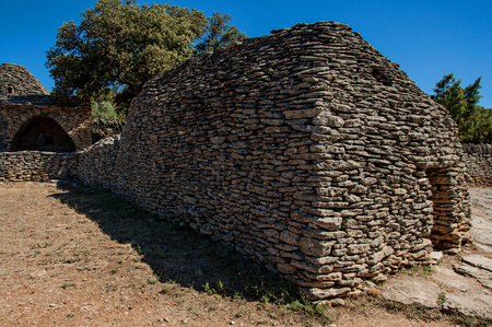 Typical hut made of stone under sunny blue sky, in the Village of Bories, near the town of Gordes. Located in the Vaucluse department, Provence region, in southeastern France