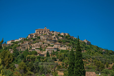 Panoramic view of the village of Gordes on top of a hill and under sunny blue sky. Located in the Vaucluse department, Provence region, southeastern France