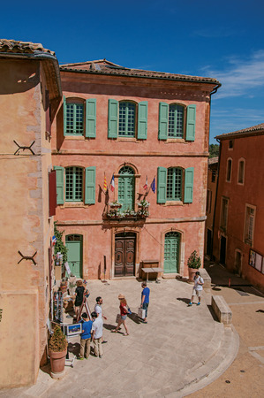 Roussillon, France - July 03, 2016. Traditional colorful houses in ocher and people in the historic city center of Roussillon. Located in the Vaucluse department, Provence region, southeastern France