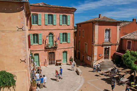 Roussillon, France - July 03, 2016. Traditional colorful houses in ocher and people in the historic city center of Roussillon. Located in the Vaucluse department, Provence region, southeastern France Editorial
