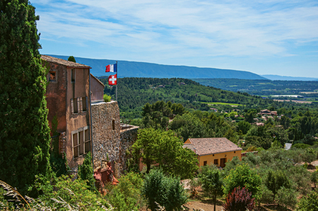 Panoramic view of the fields and hills of Provence from the city center of Roussillon, with stone houses, roofs, flags and trees. Vaucluse department, Provence region, southeastern France.