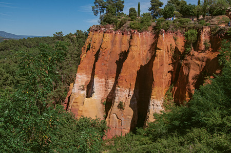 View of ocher land cliffs under a sunny blue sky, in a park near the village of Roussillon. Located in the Vaucluse department, Provence region, in southeastern France