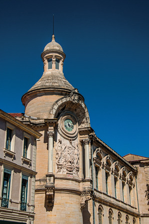 Close-up of buildings in the city center of Nimes, with clock, columns, decorative details on the walls and blue sky. Located in the Gard department, Occitanie region in southern France