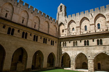 View of courtyard and internal buildings of the Palace of the Popes of Avignon, under a sunny blue sky. Located in the Vaucluse department, Provence-Alpes-Côte dAzur region, southeastern France