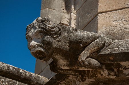 Close-up of a gargoyle on the roof of the Palace of the Popes of Avignon, under a sunny blue sky. Located in the Vaucluse department, Provence-Alpes-Côte dAzur region, southeastern France Stock Photo