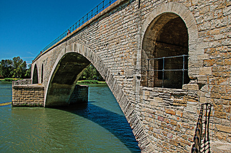 View of the Arcs of the Pont d'Avignon (bridge) under a sunny blue sky, city of Avignon. Located in the Vaucluse department, Provence-Alpes-Côte d'Azur region, southeastern France. Retouched photo