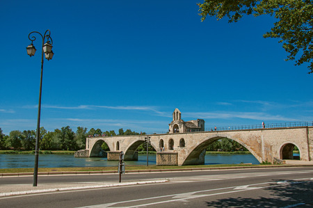 Panoramic view of the Pont dAvignon (bridge) and the Rhone River under the sunny blue sky, in the city of Avignon. In the Vaucluse department, Provence-Alpes-Côte dAzur region, southeastern France