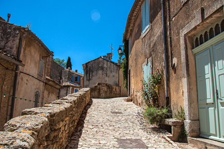 View of typical stone houses with sunny blue sky, in an alley of the historical village of Menerbes. Located in the Vaucluse department, Provence-Alpes-Côte dAzur region, southeastern France Stock Photo