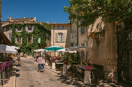 Lourmarin, France - July 07, 2016. Landscape of quiet alley with restaurants and people in the center of the lovely Lourmarin. Located in the Vaucluse department, Provence region, southeastern France