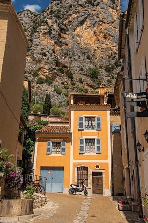 Moustiers-Sainte-Marie, France - July 08, 2016. Sunny street with shops and restaurants in the lovely village of Moustiers-Sainte-Marie. Provence region, southeastern France Editorial