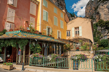 Moustiers-Sainte-Marie, France - July 08, 2016. Restaurant with flowers and cliffs in the village of Moustiers-Sainte-Marie. Alpes-de-Haute-Provence department. Provence region, southeastern France Editorial