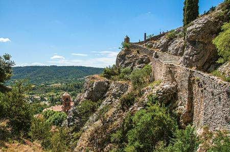 View of the path to the Notre-Dame de Beauvoir church with the graceful village Moustiers-Sainte-Marie underneath. Alpes-de-Haute-Provence department, Provence region, southeastern France