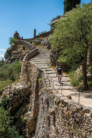 Moustiers-Sainte-Marie, France - July 08, 2016. Man walking up the staircase to the Notre-Dame de Beauvoir church, above Moustiers-Sainte-Marie village. Provence region, southeastern France