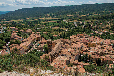 View of trees, house roofs and belfry under sunny blue sky in the charming village of Moustiers-Sainte-Marie. Located in the Alpes-de-Haute-Provence department, Provence region, southeastern France