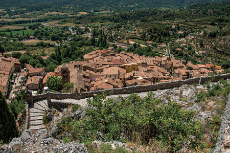 Moustiers-Sainte-Marie, France - July 08, 2016. View of stone staircase, roofs and belfry in the charming village of Moustiers-Sainte-Marie. Provence region, southeastern France Imagens