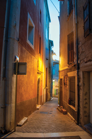 View of narrow alley in the early evening with lamp lit, in the lovely village of Rians. Located in Var department, Provence region, in southeastern France. Stock Photo