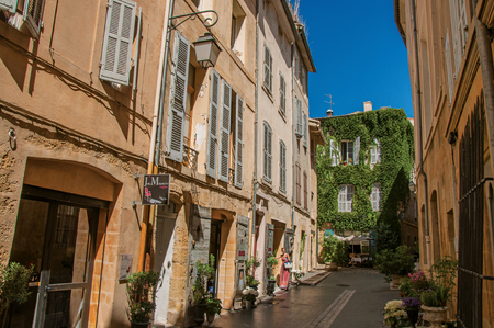 Aix-en-Provence, France - July 09, 2016. Alleyway with woman entering the house in Aix-en-Provence, a lively town in the countryside. Bouches-du-Rhone department, Provence region, southeastern France