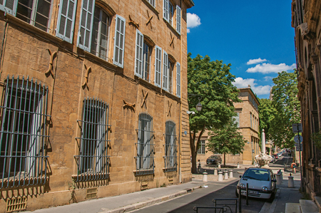 Aix-en-Provence, France - July 09, 2016. Street with buildings and shops in sunny afternoon in Aix-en-Provence, a pleasant and lively town in French countryside. Provence region, southeastern France