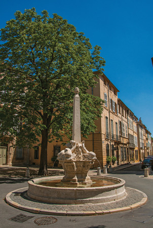 Street with buildings and fountain in sunny afternoon in Aix-en-Provence, a pleasant and lively town in the French countryside. In the Bouches-du-Rhone department, Provence region, southeastern France