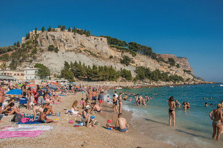 Cassis, France - July 09, 2016. Bathers on the pebble beach with castle in the background in Cassis, a beautiful and sunny seaside town with harbor. Provence region, southeastern France Editorial