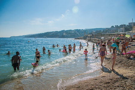 Cassis, France - July 09, 2016. Bathers on the pebble beach with sunlight in the background in Cassis, a beautiful and sunny seaside town with harbor. Provence region, southeastern France