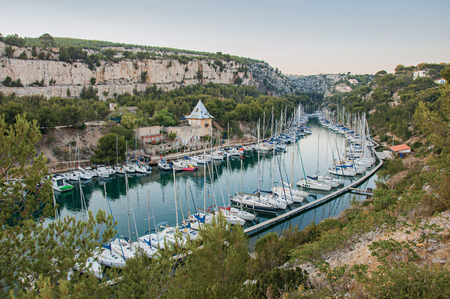 Boats anchored in a harbor inside a cliff (Calanque) near Cassis, a beautiful and sunny seaside town with harbor. Located in the Bouches-du-Rhone department, Provence region, southeastern France Stock Photo