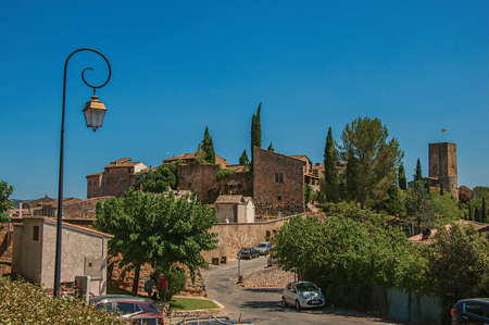 Les Arcs-sur-Argens, France - July 10, 2016. Panoramic view of the lovely hamlet of Les Arcs-sur-Argens on top of a hill and under sunny blue sky. Provence region, Var department, southeastern France Reklamní fotografie - 94872040