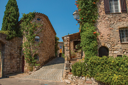 Les Arcs-sur-Argens, France - July 10, 2016. Old stone houses in alley under blue sky, at the gorgeous medieval hamlet of Les Arcs-sur-Argens. Provence region, Var department, southeastern France