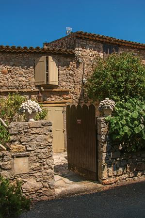 Les Arcs-sur-Argens, France - July 10, 2016. Close-up of old stone house with wooden gate, at the gorgeous medieval hamlet of Les Arcs-sur-Argens. Provence region, Var department, southeastern France Redakční