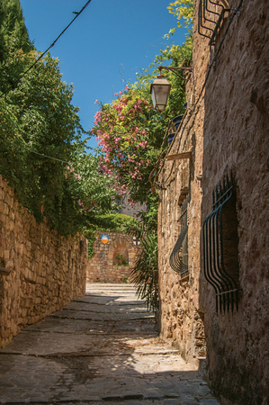 View of stone houses in a narrow alley under blue sky, at the gorgeous medieval hamlet of Les Arcs-sur-Argens, near Draguignan. Located in the Provence region, Var department, southeastern France Stock Photo
